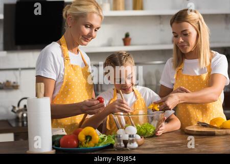 Heureux l'enfant mignon avec mère et grand-mère salade de légumes cuisson together in kitchen Banque D'Images