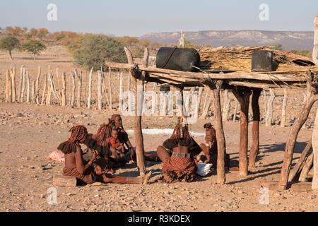 Les femmes d'un village Himba se réunissent pour discuter et préparer la nourriture dans un village près d'Opuwo.