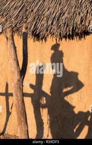 Ombre d'une femme Himba sur le côté d'une hutte de village dans un village près d'Opuwo.