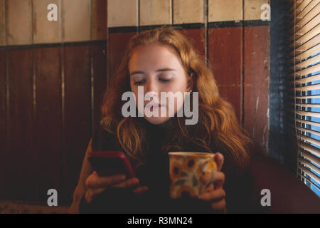 Woman using mobile phone while having coffee in cafe
