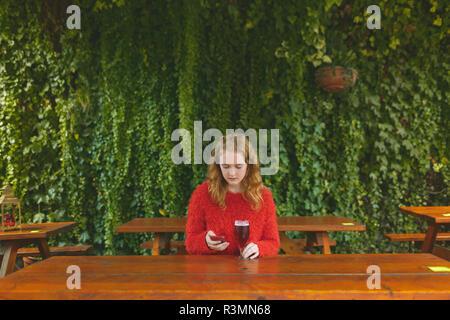 Femme à l'aide de téléphone mobile tout en ayant de la bière dans le café en plein air Banque D'Images