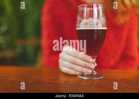 Femme tenant un verre de bière dans le café en plein air Banque D'Images