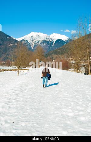 Vieux homme marche dans la neige dans une région ensoleillée et chaude journée avec panorama de la montagne Banque D'Images
