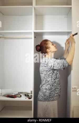 Collecte des meubles dans la chambre Caucasian middle-aged woman Banque D'Images