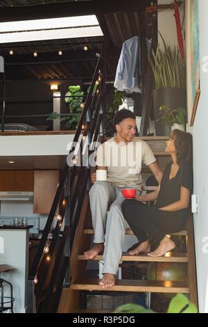 Couple en interaction les uns avec les autres tout en ayant le café dans les escaliers