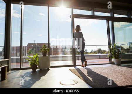 Vue arrière de la femme debout à contre-jour la fenêtre à la maison à out Banque D'Images