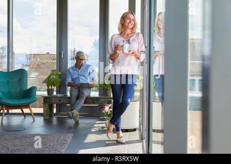 Smiling young couple relaxing at home avec femme à la fenêtre de l'homme et à l'aide de tablet