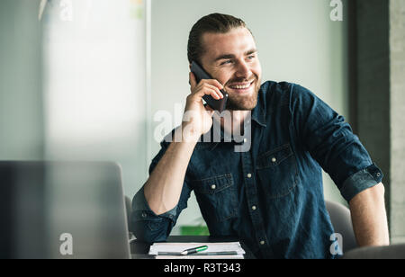 Smiling young woman on cell phone in office Banque D'Images