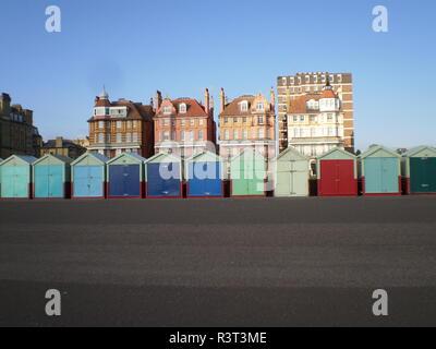 Cabines de plage colorés devant villas sur la promenade au soleil dans la ville anglaise de Brighton Banque D'Images