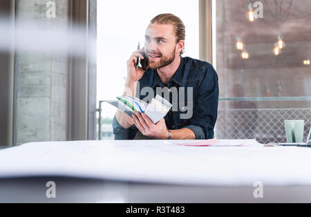Jeune homme on cell phone holding color samples at desk in office Banque D'Images