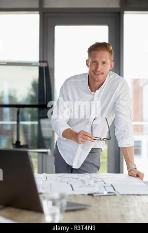 Portrait of smiling young man working on plan directeur de desk in office Banque D'Images