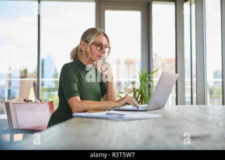Mature Woman using laptop sur la table à la maison