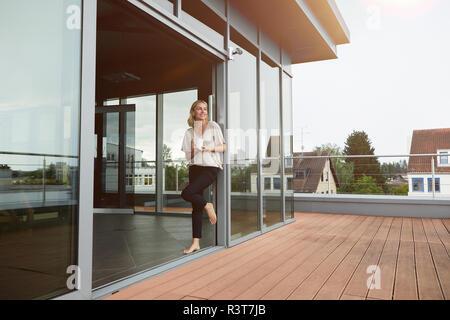 Smiling mature woman avec tasse de café debout à toit-terrasse à la maison