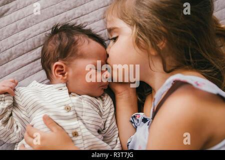 Affectueux girl lying on blanket de câlins avec son petit frère Banque D'Images
