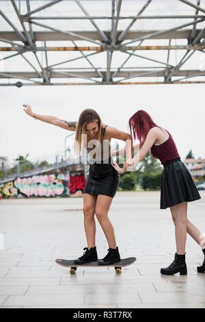 Jeune femme poussant ami sur roulettes dans la ville Banque D'Images
