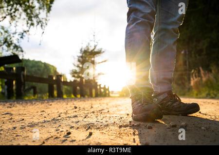 Homme debout dans la rue, au coucher du soleil, low section Banque D'Images