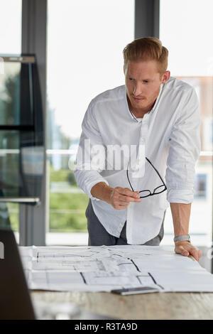 Jeune homme travaillant sur blueprint sur desk in office Banque D'Images