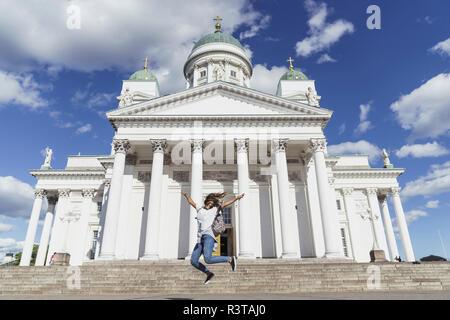 La Finlande, Helsinki, femme de sauter devant la cathédrale d'Helsinki Banque D'Images