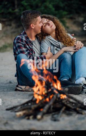 Couple assis à un feu de camp au bord de la rivière il Banque D'Images
