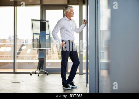 Inquiets businessman standing in office, à la fenêtre de