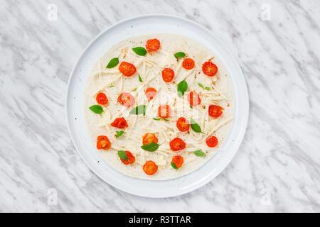 La préparation d'une tortilla avec les tomates, le fromage et le basilic. Plaque blanche sur une surface en marbre. Banque D'Images