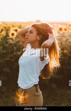 Portrait d'une jeune femme debout dans un champ de tournesols, les mains dans les cheveux Banque D'Images