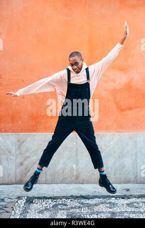 Jeune homme noir portant les tenues de saut en contexte urbain. Concept de vie. Guy africaine millénaire avec les salopettes en plein air