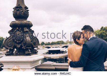 Les nouveaux mariés en voyage de noces à Paris, aimant avoir une date près de la Tour Eiffel Banque D'Images