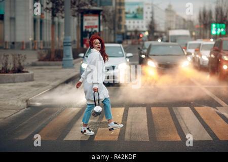 Jeune femme rousse dans un manteau blanc et bleu jeans traverse la route à un passage pour piétons. Voitures en arrière-plan.
