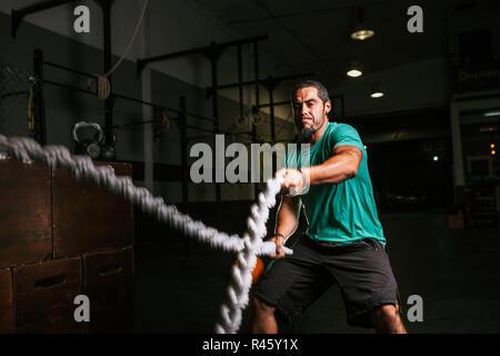 Jeune homme athlétique cross-fit faire quelques exercices avec une corde indoor Banque D'Images