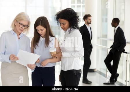 Chef d'équipe à maturité et les jeunes employés discussing paperwork dans o Banque D'Images