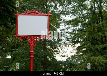 Cadre métallique décoratif rouge avec bannière blanche pour le texte. Dans l'arrière-plan les arbres avec des feuilles vertes. Banque D'Images