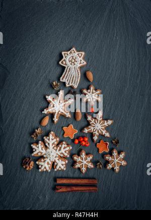 D'épices, les noix, les épices, écorce d'orange séchée créer un arbre de Noël sur un fond en pierre sombre
