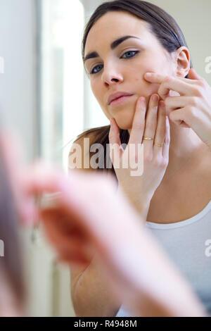 Prendre soin de sa femme la belle peau sur le visage, debout près de miroir dans la salle de bains.