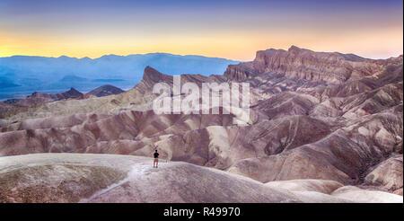Vue panoramique de l'homme bénéficiant au coucher du soleil célèbre Zabriskie Point dans la belle lumière du soir doré en été, Death Valley National Park, Californie