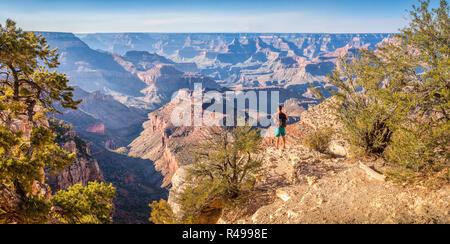 Vue panoramique de jeune randonneur donnant sur la célèbre Grand Canyon dans la belle lumière du soir d'or au coucher du soleil en été, Arizona, USA Banque D'Images