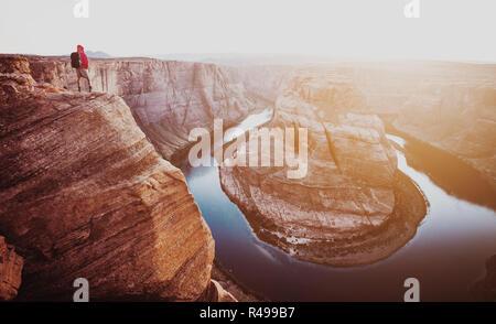 Vue panoramique de l'intrépide male hiker debout sur une falaise escarpée, tout en donnant sur célèbre Horseshoe Bend en belle lumière du soir au coucher du soleil d'or Banque D'Images