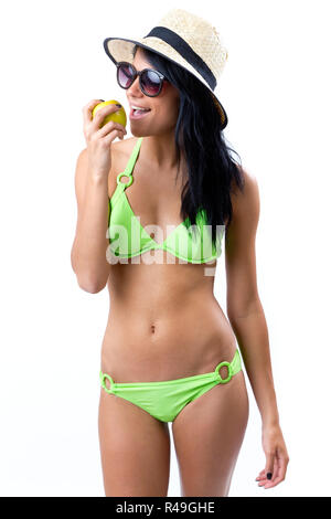 Happy Young Girl in bikini, manger une pomme Banque D'Images