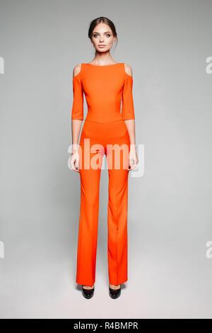 Grand modèle dans l'ensemble et orange occasionnels hauts talons. Banque D'Images