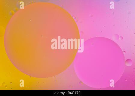 Macro photo artistique de gouttelettes d'huile flottant sur l'eau avec un fond coloré Banque D'Images