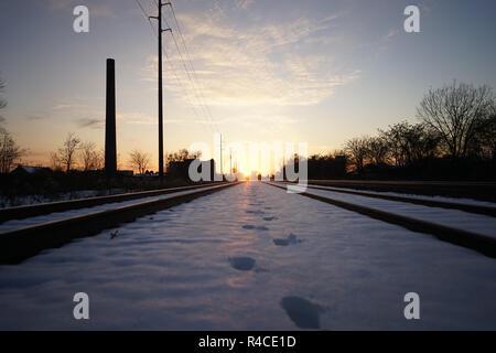 Des traces de pas dans la neige entre les voies de chemin de fer à l'heure d'or sur la côte est Banque D'Images