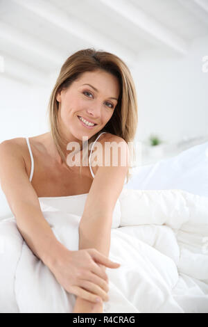 Middle-aged woman laying in bed Banque D'Images
