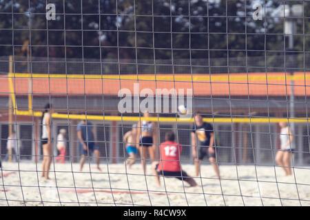 Groupe de jeunes amis joue une partie de volley-ball sur plage sur journée d'été, selectiv focus. Sport de plein air Banque D'Images