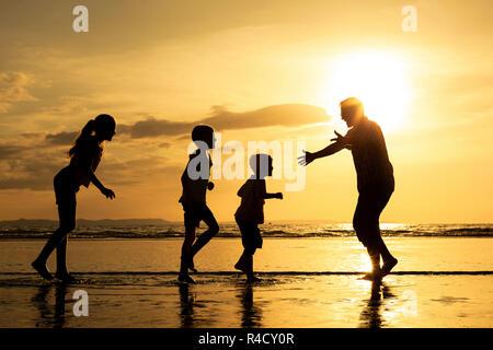 Le père et les enfants jouant sur la plage, à l'heure du coucher du soleil. Banque D'Images