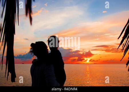 Silhouette de père et fille sur la plage au crépuscule. Banque D'Images