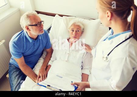 Senior woman et médecin avec presse-papiers à l'hôpital Banque D'Images