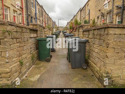 Deux lignes de wheelie bins ligne la ruelle entre deux rangées de maisons mitoyennes à Saltaire, West Yorkshire Banque D'Images