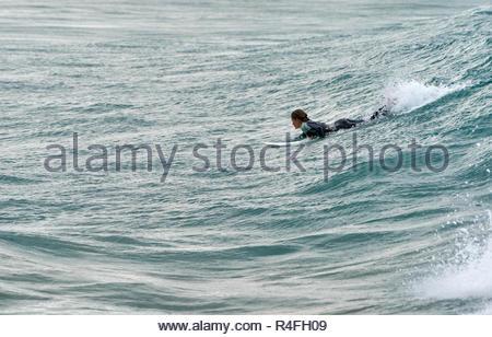 Une jeune femme en combinaison, des coups de pagaie et son surf sur une vague pendant une période de houle nice - surf au Salon Plage, Yamba, Australie. Banque D'Images