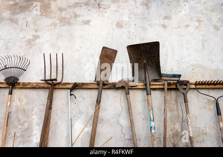 Une collection de divers outils de jardin rouillés d'occasion accrochés à un mur abîmé. Banque D'Images