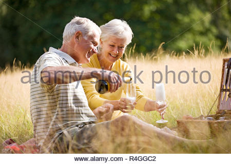 A senior couple having a picnic, man pouring champagne Banque D'Images